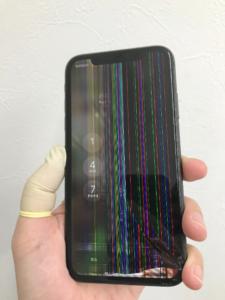 液晶が壊れたiPhoneXR。カラフルなストライプが表示されてしまっている。
